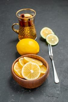 Fatias de limão fresco com chá em fundo escuro.