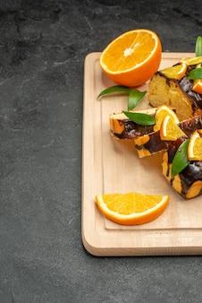 Fatias de limão fresco e fatias de bolo recém-assado na mesa escura