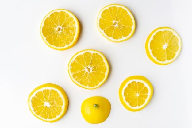 Fatias de limão repousam aleatoriamente na superfície clara da mesa.