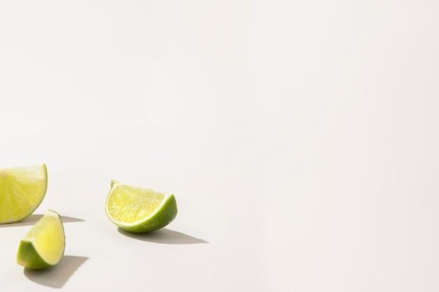 Fatias de limão verde fresco em branco