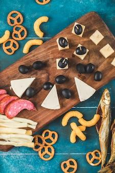 Fatias de linguiça com cubos de queijo, azeitonas e biscoitos em uma placa de madeira, vista superior