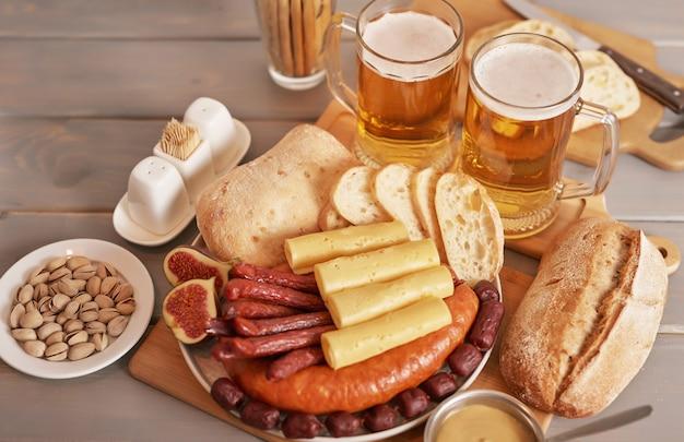 Fatias de linguiça e queijo com cerveja light e pistache para a oktoberfest