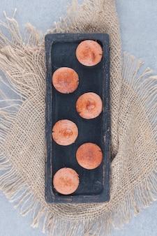 Fatias de linguiça frita fresca na placa preta.