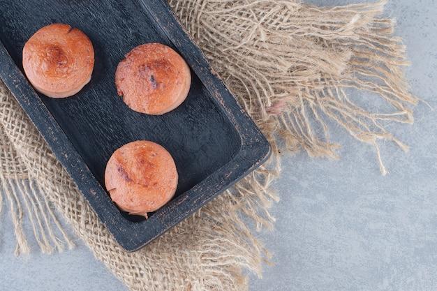 Fatias de linguiça frita fresca quente na placa de madeira preta.