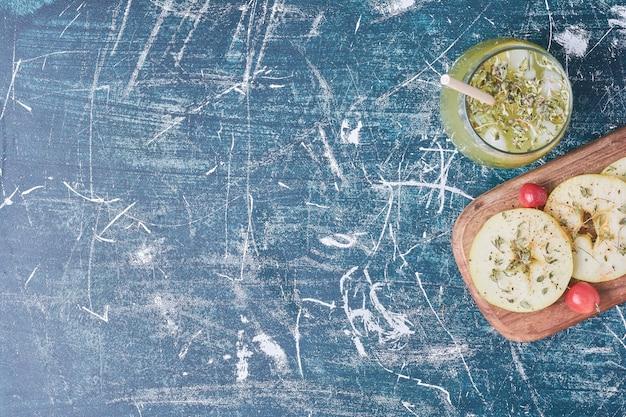 Fatias de maçã com um copo de bebida em azul.