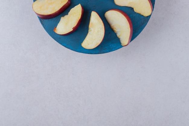 Fatias de maçã em um prato na mesa de mármore.