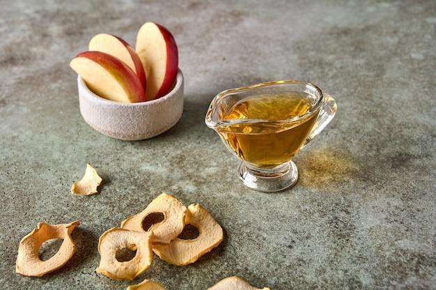 Fatias de maçã em uma tigela de batatas fritas e suco em um fundo de madeira rústico fecham o foco seletivo