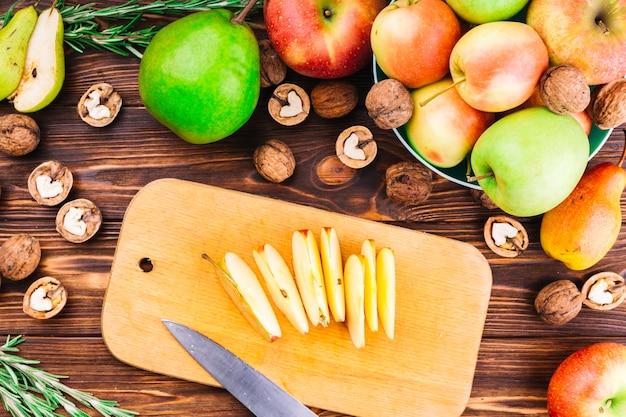 Fatias de maçã na tábua com frutas e nozes sobre a mesa