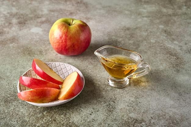 Fatias de maçã no prato, maçã, frutas e suco no fundo de madeira rústico fechem o foco seletivo