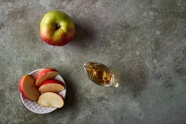 Fatias de maçã no prato, maçã, frutas e suco no fundo de madeira rústico, vista superior, espaço de cópia