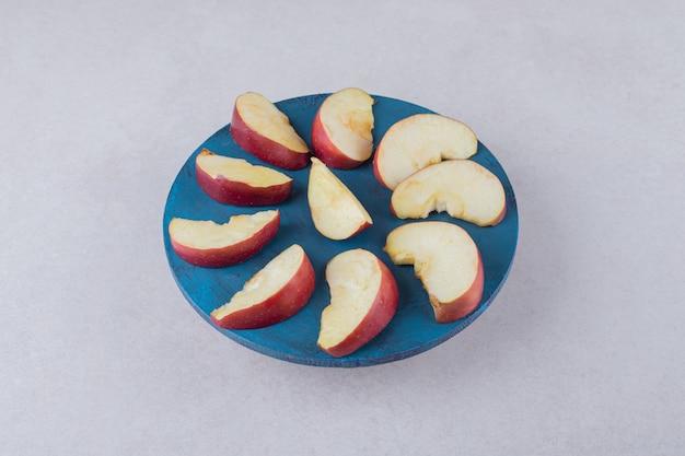 Fatias de maçã num prato, no mármore.