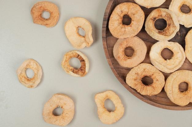 Fatias de maçã seca em prato de madeira