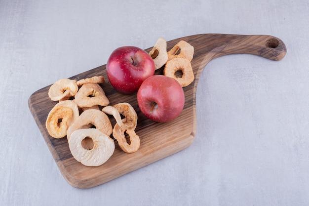 Fatias de maçã secas e maçãs inteiras em uma placa de madeira no fundo branco.