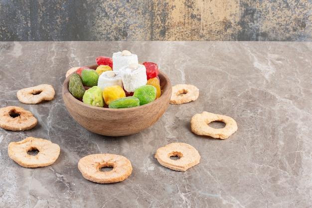 Fatias de maçã secas em torno de uma tigela de lokum e marmeladas em mármore.