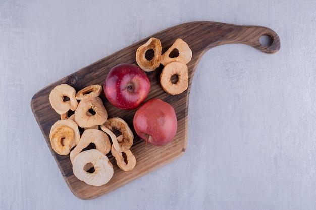 Fatias de maçã secas suculentas e maçãs inteiras em uma placa de madeira no fundo branco.