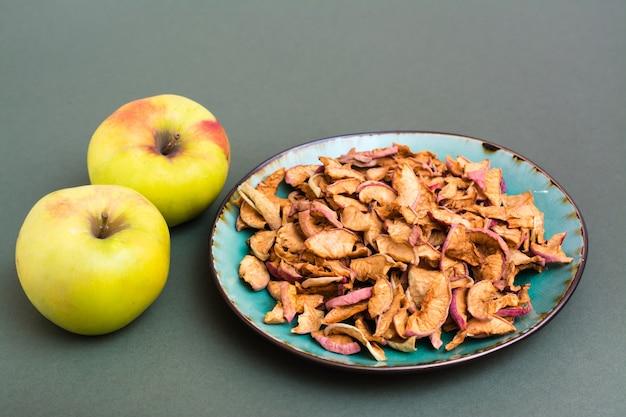 Fatias de maçãs secas em um prato e maçãs frescas em um fundo verde. alimentação saudável