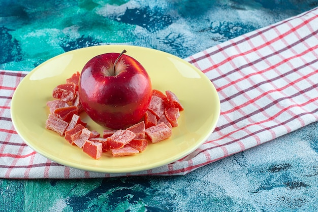Fatias de marmelada vermelha e maçã em um prato no pano de prato, na mesa azul.