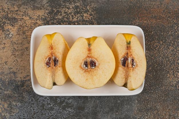 Fatias de marmelo amarelo em prato quadrado branco
