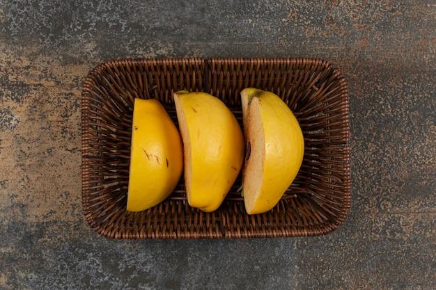 Fatias de marmelo amarelo na cesta de madeira