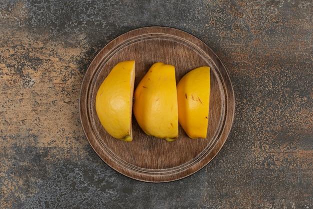Fatias de marmelo fresco na tábua de madeira