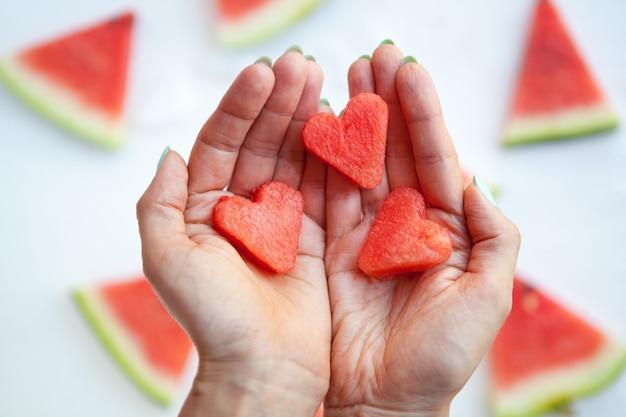 Fatias de melancia de coração nas mãos da mulher espalmadas colocam fatia de melancia no conceito de amor e cuidado branco