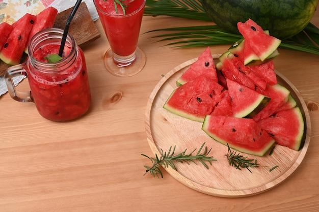 Fatias de melancia e smoothie em frasco de vidro na mesa de madeira.
