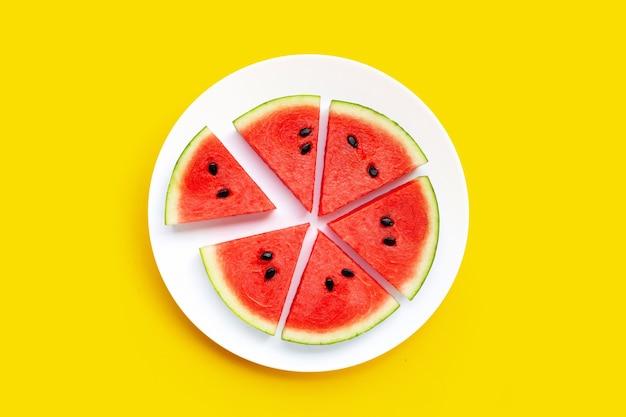 Fatias de melancia em chapa branca sobre fundo amarelo.