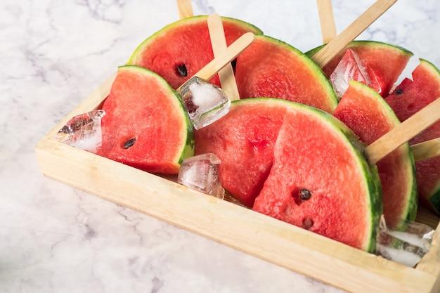 Fatias de melancia em palitos com cubos de gelo. picolés de melancia fresca em uma tigela de madeira.
