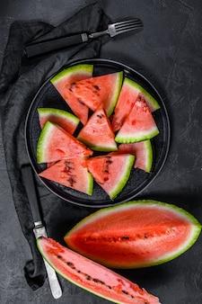 Fatias de melancia em um prato no escuro