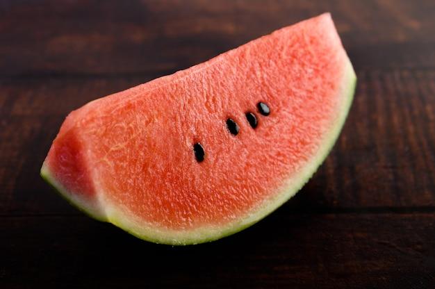 Fatias de melancia em uma mesa de madeira.