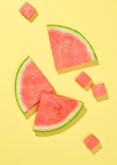 Fatias de melancia fresca e pedaços isolados em fundo amarelo, vista superior