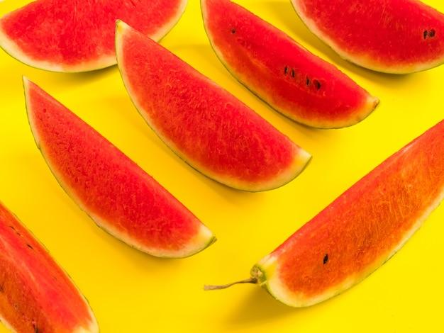 Fatias de melancia madura fresca em fundo amarelo.