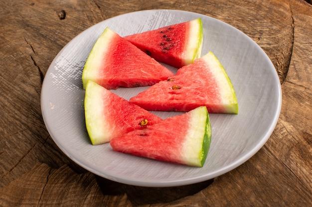 Fatias de melancia pedaços frescos e maduros dentro do prato no marrom