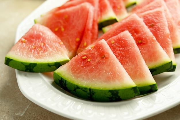 Fatias de melancia sem sementes em um prato. alimentos deliciosos de verão, lanche saudável.