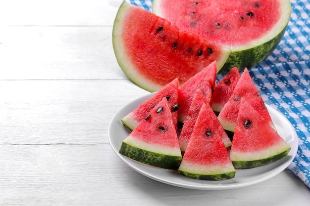 Fatias de melancia vermelha em um prato e meia melancia em uma mesa de madeira branca