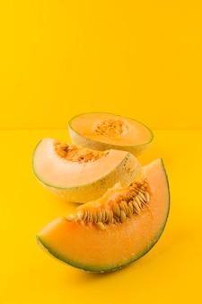 Fatias de melão fresco maduro em fundo amarelo