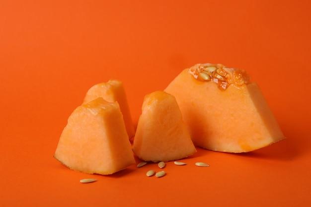 Fatias de melão maduro em fundo laranja, close-up