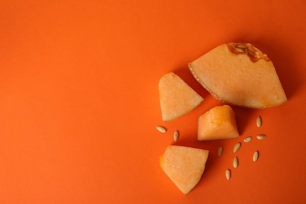 Fatias de melão maduro em fundo laranja, vista superior