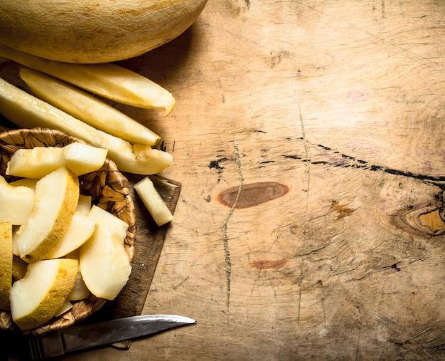 Fatias de melão maduro em uma cesta com uma faca