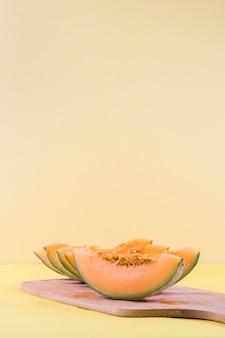Fatias de melão na tábua de madeira contra o pano de fundo bege