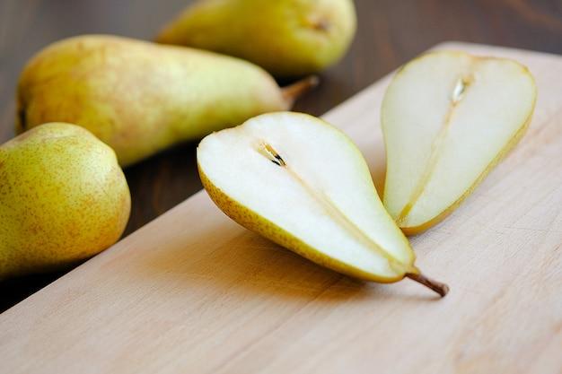 Fatias de metades ou fatias de peras maduras frescas amarelas e verdes maduras, próximas pêras inteiras e tábua de cozinha de corte