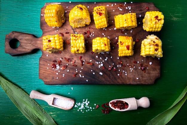 Fatias de milho grelhado na placa de madeira com sal e pimenta vermelha,