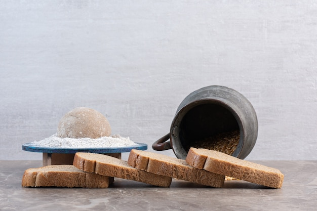 Fatias de pão, bandeja de farinha e jarro de trigo em mármore.