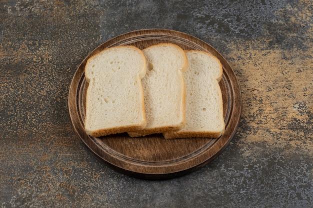 Fatias de pão branco caseiro na placa de madeira.