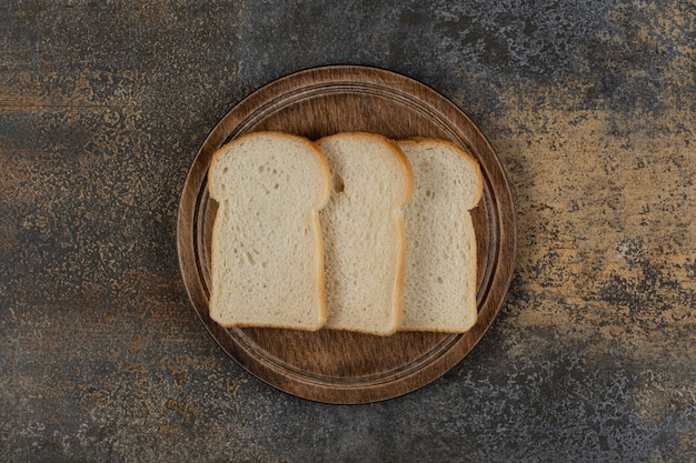 Fatias de pão branco caseiro na tábua de madeira