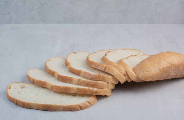 Fatias de pão branco fresco no fundo de mármore.