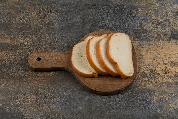 Fatias de pão branco na tábua de madeira