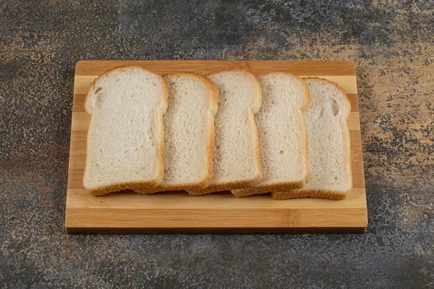 Fatias de pão caseiro na placa de madeira.