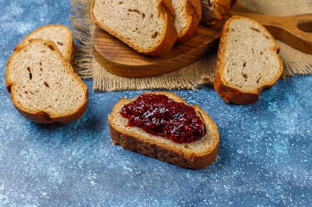 Fatias de pão com geléia de framboesa, lanche saudável fácil, vista superior