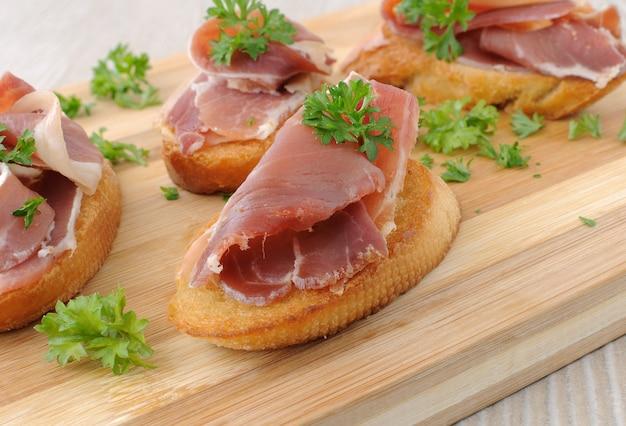 Fatias de pão com jamon serrano espanhol em uma placa de madeira